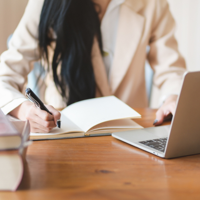 Woman writing in notebook with laptop and stack of books in front of her
